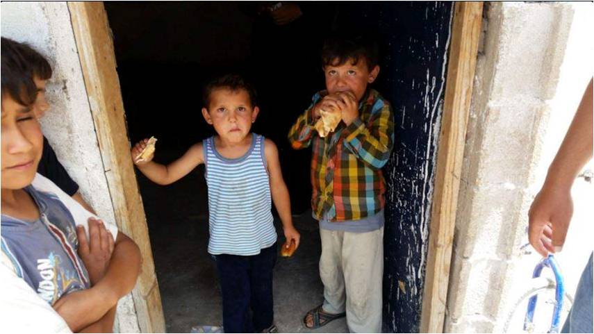 Handing out bread to Syrian children in a refugee camp in Turkey near the Syrian Border