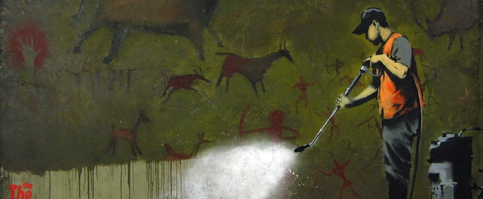 Graffiti piece of a cleaner removing cave paintings by Banksy